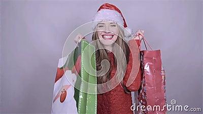 De holding van het kerstmanmeisje het winkelen zakken, die van sneeuwval in studio genieten stock video