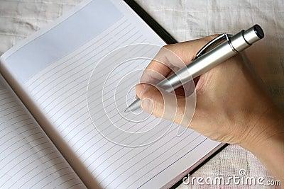 De holdingspen die van de hand op notaboek schrijft