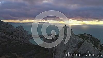 De hommel vliegt snel achteruit over de klimmermens die zich bovenop rots bij zonsopgang bevinden Lucht Mening stock video