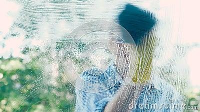 De huisvrouw in overhemd veegt glazen venster met blauw nat vod af stock videobeelden