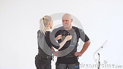 De hulpmens van de blonde vrouwelijke trainer om elektrode op EMS-kostuum vast te maken stock video