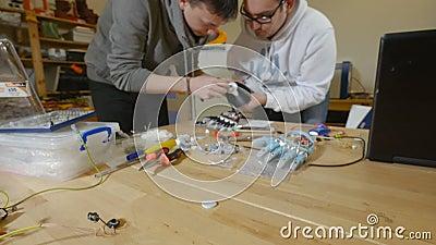De ingenieurs in laboratorium bespreken robotachtig bionisch die wapen op 3D printer wordt gemaakt stock footage