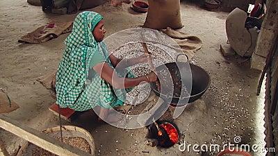 De inwoner van Bangladesh vrouw produceert droge gebraden rijst op heet zand in een traditionele stijl in Tangail, Bangladesh stock videobeelden
