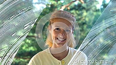 De jonge Aantrekkelijke Vrouw wast een Venster Glimlachend bij de Camera Dolly schot stock videobeelden