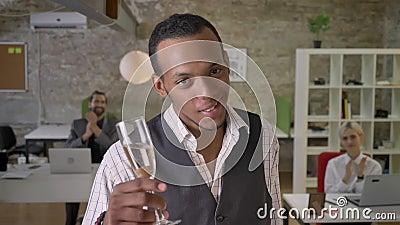 De jonge Afrikaanse zakenman bevindt zich en houdend glas champagne in bureau, slaat het glimlachen, collega's stock videobeelden