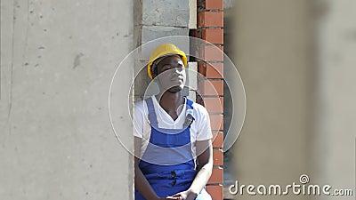 De jonge Afro-Amerikaanse bouwvakker neemt een onderbreking tijdens het werk stock videobeelden