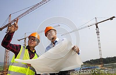 De jonge Aziatische voorzijde van de architectenbespreking van bouwwerf
