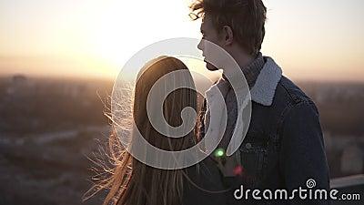 De jonge blondy jongen en haar langharig meisje bevinden zich op roog tijdens zonsopgang het omhelzen Genieten van stock video