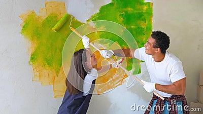 De jonge familie maakt reparaties in nieuwe vlakte Paar - het schilderen muur in flat Man en vrouw die revisie van huis doen stock videobeelden