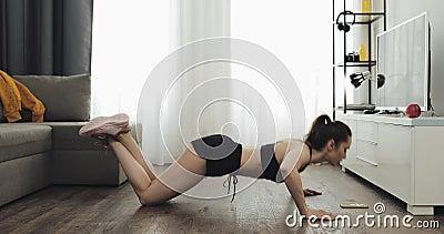 De jonge geschiktheidsvrouw in atletische training kleedt het doen van oefening ush-UPS terwijl het gebruiken van een chronometer stock videobeelden