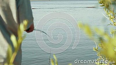 De jonge hengel van de vissersholding met vlotter die op beet achtermening wachten stock video