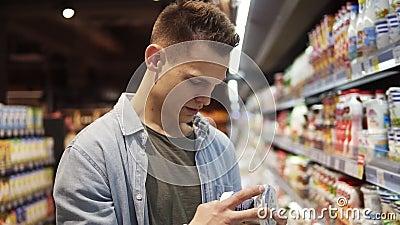 De jonge man kiest jogurt of zure room in de supermarkt, de klant selecteert het product op de schappen van zuivelproducten in de stock videobeelden