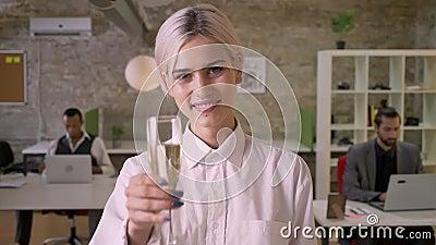 De jonge mooie onderneemster bevindt zich en houdend glas champagne in bureau, werken de collega's met laptops stock videobeelden