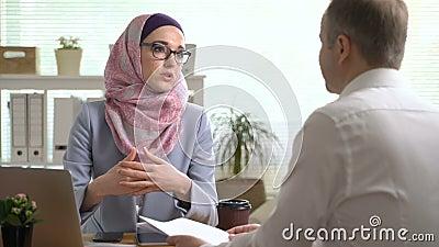 De jonge moslimhanden van de bedrijfsvrouwenschok met een Kaukasische man tijdens een vergadering in bureau stock footage