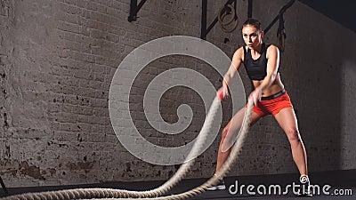 De jonge volwassen meisje het praktizeren oefening van de slagkabel tijdens een dwars geschikte training bij de gymnastiek, stock video