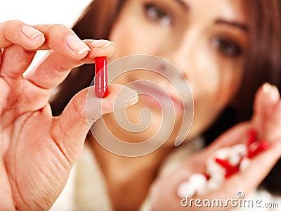 De jonge vrouw die griep heeft neemt pillen.