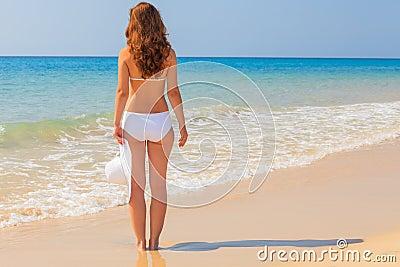 De jonge vrouw geniet van zon op het strand