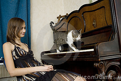De jonge vrouw let op kat lopend op piano