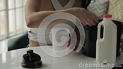 De jonge vrouw zet proteïne in schudbeker terwijl het zitten van huis stock video