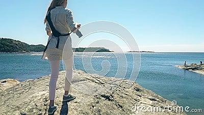 De jonge vrouwelijke fotograaf beklimt een klip boven het overzees om een foto te nemen stock video