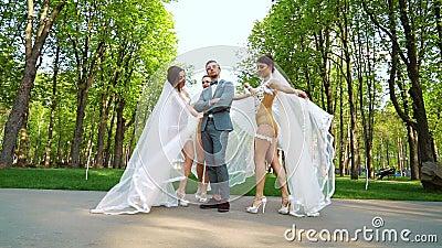 De jonge vrouwen in sexy bruids kostuums dansen rond de mens die zich nog in park bevinden stock footage