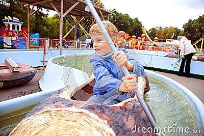 De jongen die van de aantrekkelijkheid in de boot zwemt