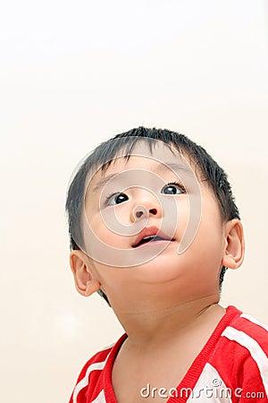 De jongen die van de baby omhoog kijkt