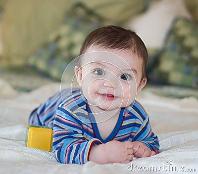 De Jongen die van de baby terwijl het Stellen glimlacht
