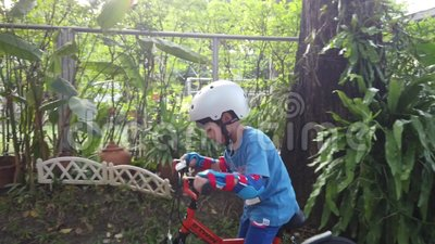 De jongen leert om een fiets met volledige bescherming met zongloed te berijden stock footage