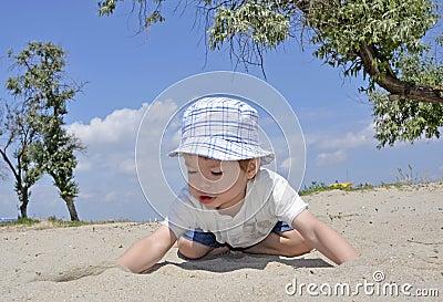 De jongen van de baby het spelen in zand op strand