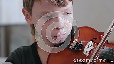 De jongen van 8 jaar leert om viool te spelen stock footage