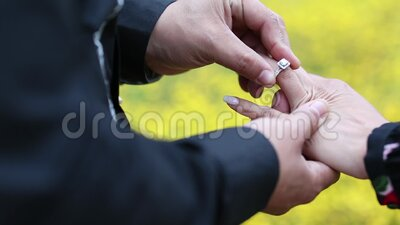 De jongen zet de verlovingsring op de vinger van het meisje stock video
