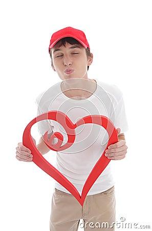 De jongens rood hart die van de tiener omhoog kussende valentijnskaart