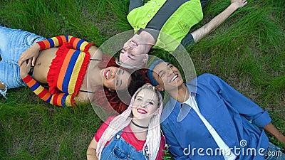 De joyeux amis multiraciaux couchés ensemble dans le parc, connexion à la liberté des jeunes clips vidéos