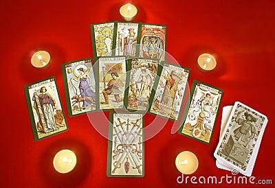 De kaarten van het tarot met kaarsen op rode textiel