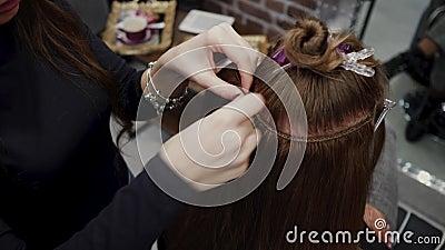De kapper naait kunstmatig haar aan het echte ding Het proces van haaruitbreiding 4K stock videobeelden