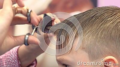 De kapper snijdt klappen met schaar op het hoofd van de jongen De handenclose-up van de stilist, zijaanzicht stock video