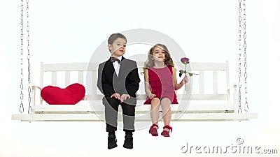 De kinderen berijden op een schommeling, hebben zij een romantische verhouding Witte achtergrond Langzame Motie stock videobeelden