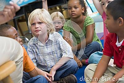 De kinderen die van de kleuterschool aan een verhaal luisteren