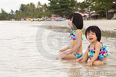 De kinderen genieten van golven op strand