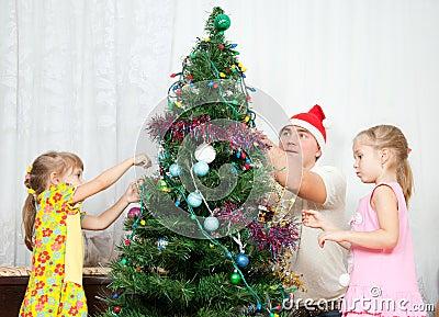 De kinderen verfraaien de Kerstboom
