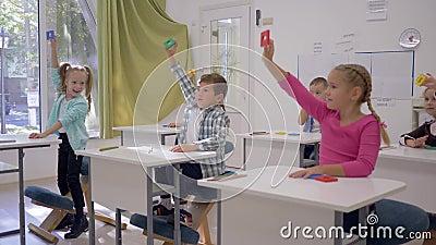 De kinderenontwikkeling, geleerden heft geometrische vormen in handen tijdens les in klaslokaal van Lage school op stock videobeelden