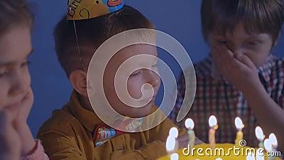 de kleine jonge geitjes zitten bij rode lijst met cake en slag in veelkleurige partijventilators bij verjaardagspartij Gelukkige  stock video