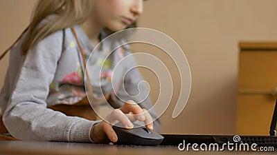 De kleine kindhand houdt een computermuis op het scherm van laptop achtergrond Online onderwijs op afstand tijdens quarantaine en stock footage