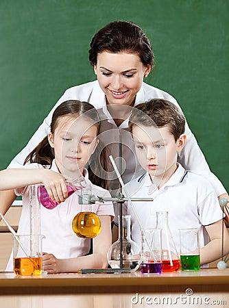 De kleine leerlingen gieten chemische vloeistoffen