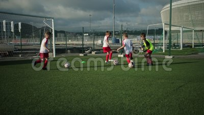 De kleine voetballers drijven ballen op voetbalveld stock footage