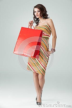 De kleurrijke uitrusting die van de vrouw rode het winkelen zak houdt