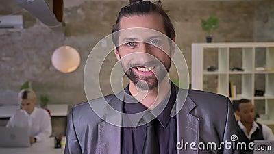 De knappe zakenman met baard let op bij camera in bureau, het glimlachen, werken de collega's met laptops, het werk stock footage