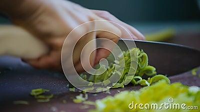 De kok die de groene ui op de raad snijden stock footage