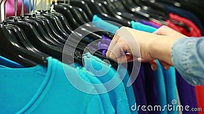 De koper kiest een T-shirt in een boutique stock footage